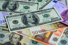 Dollar und Eurobanknotegeldhintergrund Stockfotos