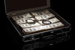 Dollar und Handschellen im Koffer lokalisiert auf Schwarzem Lizenzfreies Stockfoto