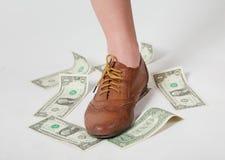Dollar under boots Stock Photo