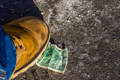 Dollar under boots on the ground Royalty Free Stock Photos