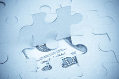 Dollar under puzzle Stock Photo