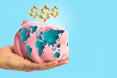 Dollar unterzeichnen vorbei Sparschwein mit worldmap in der männlichen Hand Lizenzfreie Stockfotos