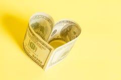 Dollar US bills in heart shape. On yellow Stock Photo