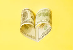 Dollar US bills in heart shape. On yellow Royalty Free Stock Photography