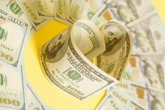 Dollar US bills in heart shape. On yellow Stock Photos