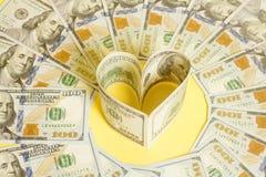 Dollar US bills in heart shape. On yellow Stock Image