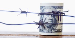 Dollar US enveloppé en barbelé comme symbole de la guerre économique, photo libre de droits