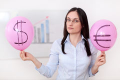 Dollar versus Euro. A young woman is holding two balloons marked with the dollar and euro symbols with an ascending chart in the background Stock Images