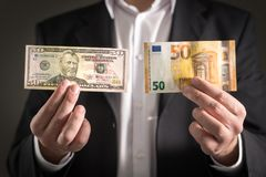 Dollar vs euro. Business man in suit holding 50 banknote and bill in both currency in hand. Exchange rate, world economy and financial concept stock photography