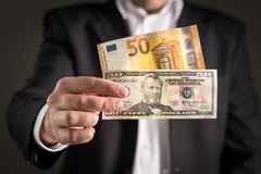 Dollar vs euro. Business man in suit holding 50 euros. Dollar vs euro. Business man in suit holding 50 banknote and bill in both currency in hand. Exchange rate royalty free stock images
