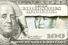 Dollar vs. Yuan. Torn hundred dollar bill with Mao from yuan stock images