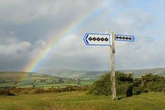 Dollar-Zeichen auf Signpost, Regenbogen im Hintergrund. Stockfotografie