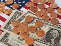 Dollaranmärkningar och mynt och flagga av Förenta staterna Arkivfoto