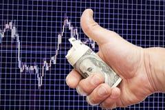 Dollaranmerkungen in der Hand über einen blauen Hintergrund mit dem Zeitplan Stockfotografie