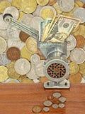 Dollarbankbiljetten in gehaktmolen en muntstukken op lijst aangaande partij van Di Stock Fotografie