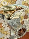 Dollarbankbiljetten in gehaktmolen op partij van verschillende muntstukken backg Stock Foto's