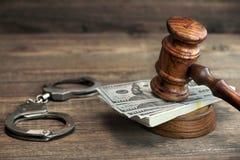Dollarbankbiljetten, handcuffs en rechtershamer op houten lijst stock afbeeldingen