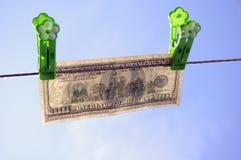 Dollarbanknote hängt an einem Netzkabel stockfotos