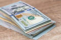 Dollarbanknote mit 100 Amerikanern auf Schreibtisch Stockbilder