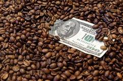 Dollarbanknote mit 100 Amerikanern in den Röstkaffeebohnen Lizenzfreies Stockfoto