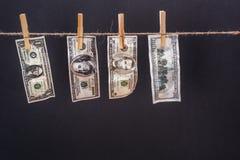 Dollarbanknoten, die am Seil lokalisiert auf Schwarzem hängen Lizenzfreie Stockbilder