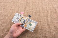 Dollarbanknoten mit einem Herzen befestigen auf einer Schnur Lizenzfreie Stockfotos