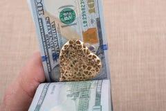 Dollarbanknoten mit einem Herzen befestigen auf einer Schnur Stockbilder