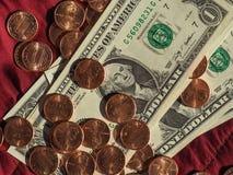 Dollarbanknoten und Münze, Vereinigte Staaten über rotem Samthintergrund Lizenzfreie Stockbilder