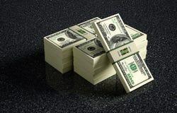 100 Dollarbanknotenbündel auf gemarmortem Boden Stockfoto