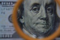 Dollaren ökar till och med ett förstoringsglas, kontrollen för falskhet Arkivbilder