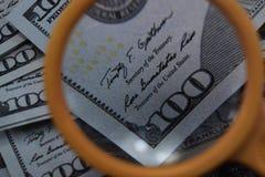 Dollaren ökar till och med ett förstoringsglas, kontrollen för falskhet Royaltyfria Foton