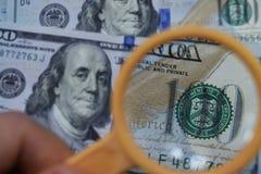 Dollaren ökar till och med ett förstoringsglas, kontrollen för falskhet Arkivfoto