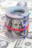 Dollaren rullar upp med rött gummi Arkivbild