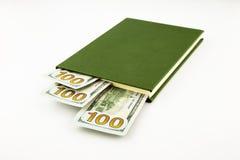 Dollargeldbanknoten und -buch Stockfotos