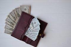 Dollargeldbanknoten und -geldbörse auf dem weißen hölzernen Hintergrund Amerikanisches Bargeld Muster von 5000 Rubeln Rechnungen  Stockbilder
