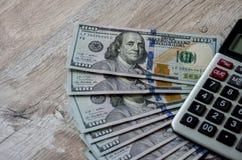 Dollari americani e un calcolatore su un fondo di legno fotografia stock libera da diritti