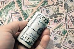 50 dollari americani hanno creato la struttura e la persona del fondo che tengono la moneta del rotolo a disposizione immagini stock