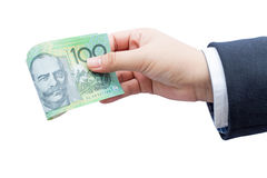 Dollari australiani del rotolo della tenuta della mano dell'uomo d'affari (AUD) Immagine Stock