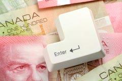 Dollari canadesi e un tasto di immissione Fotografia Stock Libera da Diritti