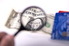 Dollari, carte assegni e lente Fotografia Stock