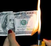 100 dollari che bruciano su un fondo nero Fotografie Stock Libere da Diritti