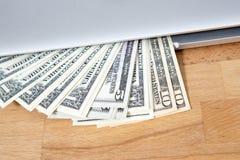 Dollari che mostrano fuori dal computer portatile Fotografia Stock Libera da Diritti