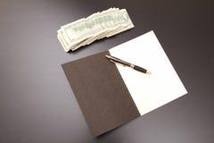 Dollari con un quaderno Fotografia Stock