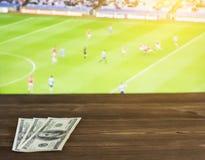 Dollari dei soldi sui precedenti della TV su cui calcio gaelico di manifestazione, sport che scommettono, dollari, Gaelic Footbal fotografie stock libere da diritti