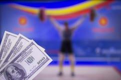 Dollari dei soldi sui precedenti della TV su cui sollevamento pesi di manifestazione, sport che scommettono, sollevamento pesi, d fotografia stock