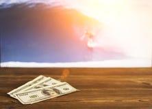 Dollari dei soldi sui precedenti di una TV su cui manifestazione che pratica il surfing, sport che scommettono, surf, dollari fotografia stock