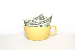 Dollari delle banconote in tazza gialla su un fondo bianco Fotografia Stock