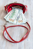 100 dollari di banconote cadono fuori dalla borsa rossa Fotografia Stock