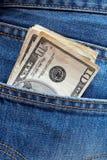 Dollari di fatture in una casella dei jeans Fotografia Stock