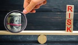 """Dollari e l'iscrizione """"rischio """"sulle scale Il concetto del rischio finanziario e di investimento in un progetto di affari Fabbr fotografia stock"""